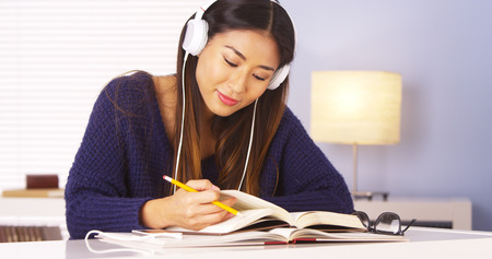 Asian woman listening to music while doing homework Archivio Fotografico