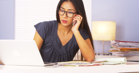 Japanese businesswoman talking on smartphone while doing paperwork photo