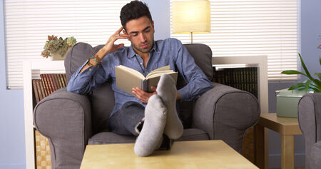 mature mexican: Attractive Latino reading a book at home