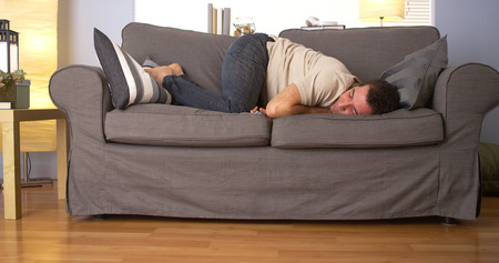 Man trying to sleep on couch