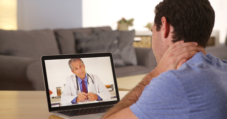 medical doctors: Man using laptop to talk to doctor