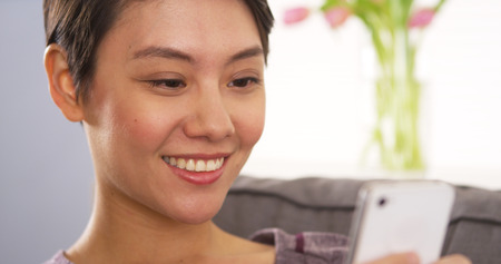 Asian woman talking on smartphone with webcam Stock Photo