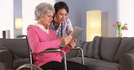 home health care: Elderly patient and Asian nurse talking with tablet
