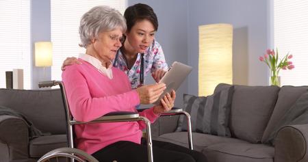 chăm sóc sức khỏe: Người cao tuổi bệnh nhân và y tá Châu Á nói chuyện với máy tính bảng