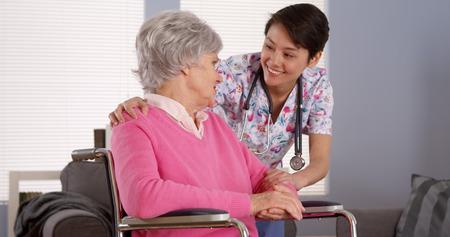 Aziatische verpleegster praten met hogere patiënt