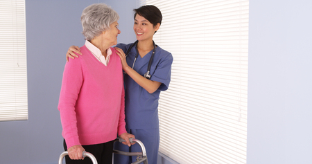 Asian nurse and elderly patient standing by window photo