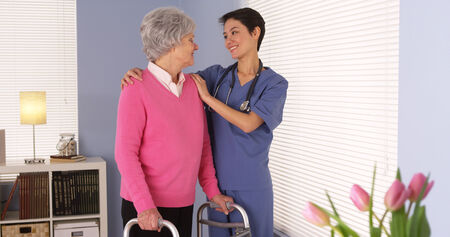 Chinese nurse talking with elderly patient by window photo