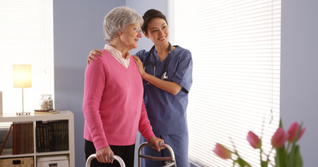 Chinese nurse and elderly woman patient looking out window Standard-Bild
