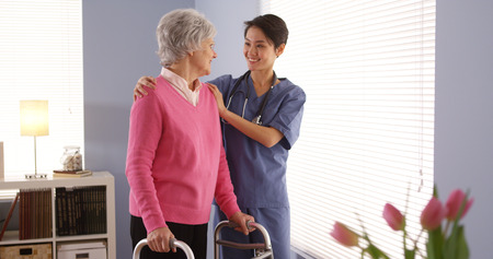 Asian nurse and elderly woman patient looking out window photo