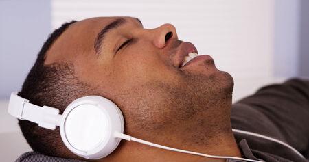 Black man listening to music with headphones photo