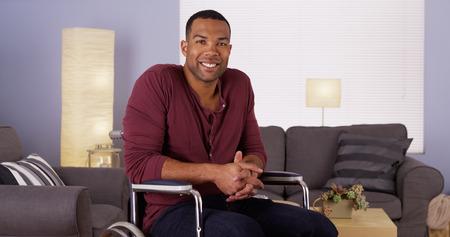 Šťastný africký muž sedící na invalidním vozíku s úsměvem