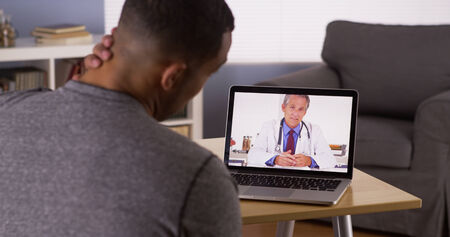 Black patient discussing health problems with doctor online Reklamní fotografie