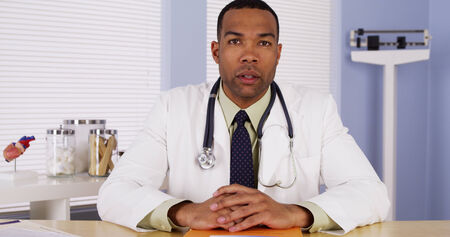 consulting room: Black doctor listening and talking to camera