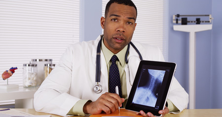 Black doctor reviewing neck x-ray
