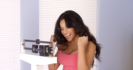 Hispanic woman happy on scale Stock Photo