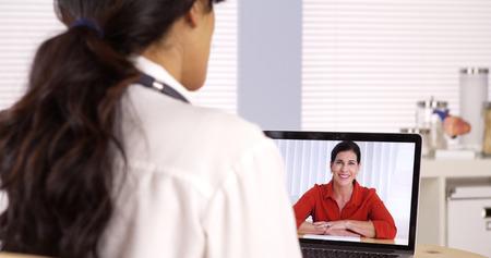 Hispanic doctor talking patient on laptop