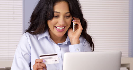 Hispanic woman making a purchase over the phone photo