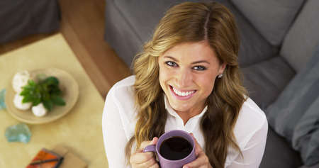 Pretty smiling girl drinking cup of coffee at home photo