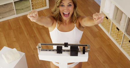 scale weight: Happy woman celebrating weight loss