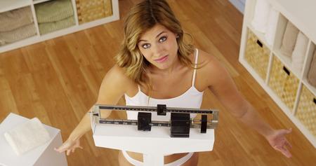 Frustrierte Frau mit der Gewichtszunahme unglücklich