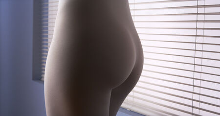 leggings: Close up mid section of woman standing by window Stock Photo