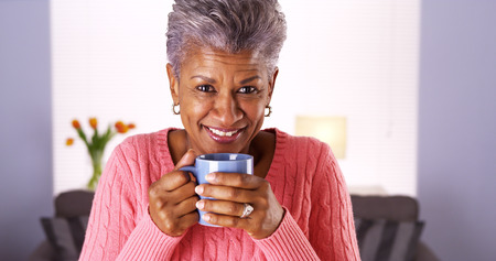 older women: Mature black woman smiling with coffee mug Stock Photo