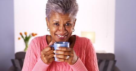 black: Mature black woman smiling with coffee mug Stock Photo