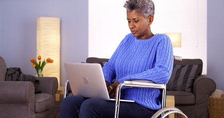 Mature Black woman sitting in wheelchair with laptop photo