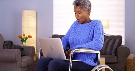 wheel house: Mature African woman sitting in wheelchair with laptop Stock Photo