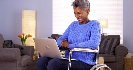 Mature African woman talking with friend on laptop Standard-Bild