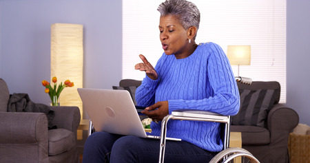 Mature Black woman talking with friend on laptop