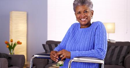 Glückliche fällige schwarze Frau sitzt im Rollstuhl