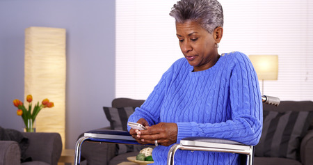 Mature black woman texting on smartphone photo
