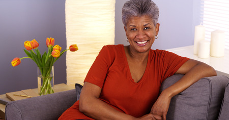 woman on couch: Cheerful African grandmother sitting on couch Stock Photo