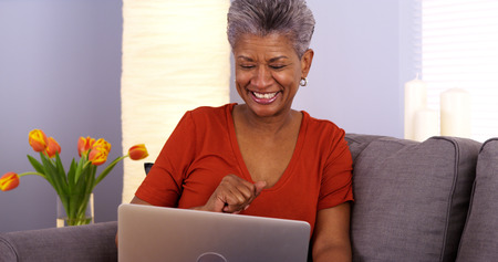 Black grandmother laughing and talking on laptop