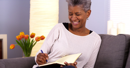 Mature black woman writing in journal Stockfoto