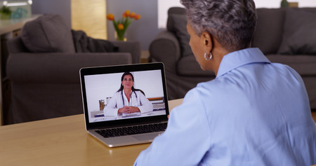 chat: Mature African woman talking to doctor on laptop