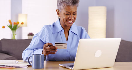 managing money: Mature Black woman happily paying her bills