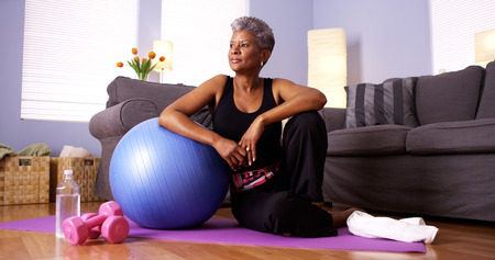 older women: Senior Black woman sitting on floor with exercise equipment Stock Photo