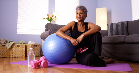 Senior African woman sitting on floor with exercise equipment photo