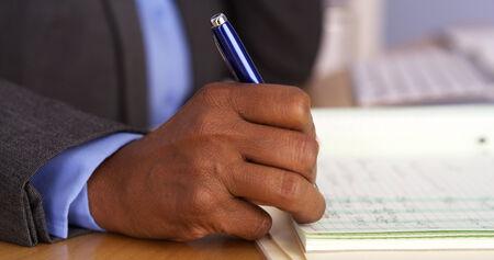 taking notes: Senior black businesswoman taking notes on pad Stock Photo