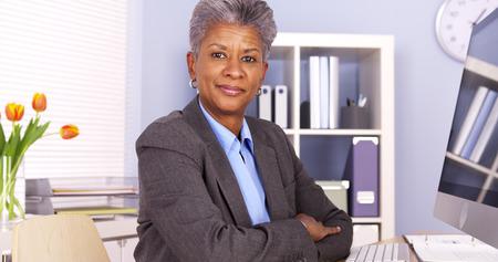 Mature African businesswoman sitting at desk Archivio Fotografico