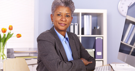 Mature African businesswoman sitting at desk Stok Fotoğraf
