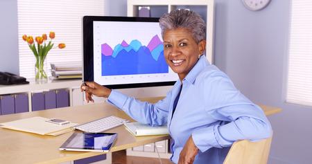 Glückliche ältere afrikanische Geschäftsfrau sitzt am Schreibtisch