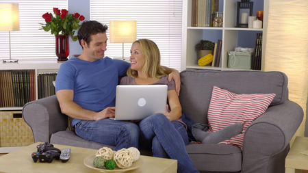 couple on couch: Cute couple sitting on couch with laptop Stock Photo