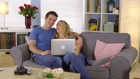 couple couch: Happy couple sitting on couch with laptop Stock Photo