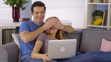 couple on couch: Couple laughing with laptop on couch