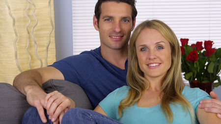 sweet couple: Sweet couple sitting on couch looking at camera