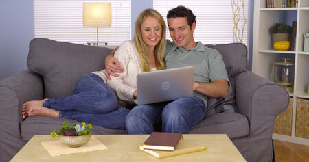 laptop: Happy couple using laptop on couch Stock Photo