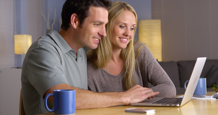 getaways: Cute couple looking for vacation getaways on laptop
